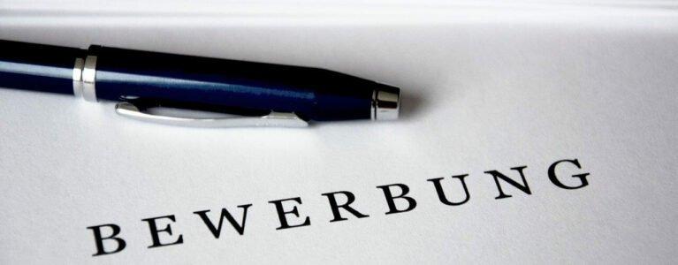 """Ein Stift liegt auf einem Papier mit der Überschrift """"Bewerbung"""""""