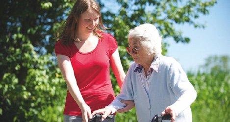 Eine Frau hilft einer alten Frau beim gehen